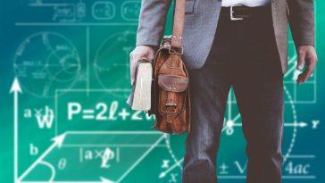 erkek öğretmen elinde çantası tahtanın önünde duruyor